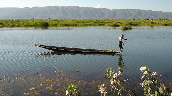 """Ein Mann, ein Boot: Die Intha, die """"Leute vom See"""", bewegen sich mit kräftigen Paddelstößen über die Wasseroberfläche."""