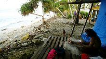 Ein Fisc her sitzt vor seinem Haus am Strand von Funafuti auf Tuvalu.