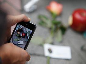 Kommunikation heute: Ein Iphone-Nutzer macht ein Foto von Beileidsbekundungen - und stellt es womöglich kurz danach in Netz.