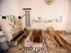Angehörige von Gaddafis Stamm stehen an den geschändeten Gräbern.