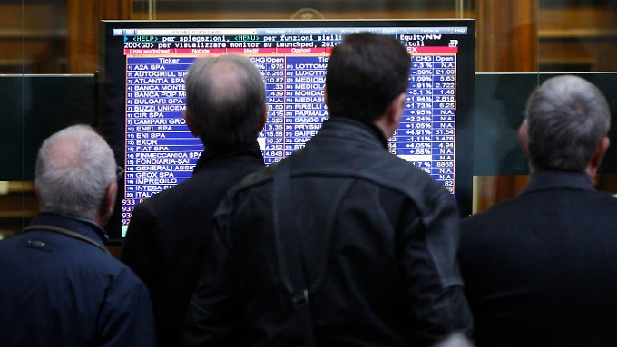 Passanten blicken an der Mailander Börse auf einen Monitor mit Kursinformationen.