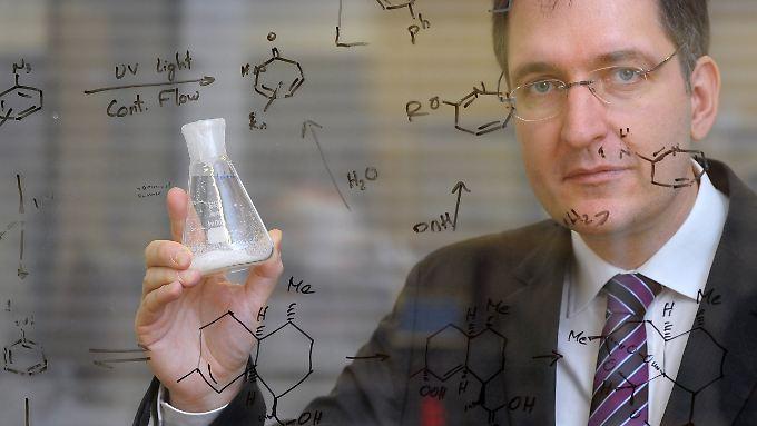 Peter H. Seeberger, Direktor am Max-Planck-Institut, zeigt in einem Labor hinter einer Glasscheibe, auf der unter anderem die Formel zur Synthese des Wirkstoffes Artemisinin aufgeschrieben ist, eine Probe des Stoffes.