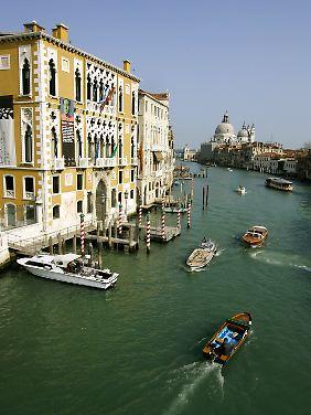 Blick über den Canal Grande mit rot-weiß markierten Anlegestellen für die traditionellen Gondeln.