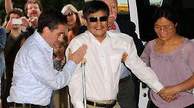 Gestützt von seiner Frau und einem Helfer wird Chen Guangcheng in den USA in Empfang genommen.
