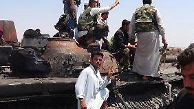 Kämpfer der Freien Syrischen Armee posieren in Idlib vor einem zerstörten Panzer der Regierungstruppen.