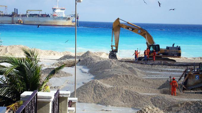 """Bagger verteilen weißen Sand an den Stränden Cancuns. Der Saugbagger hinten holt Tausende Kubikmeter Sand von den Bänken der Insel Cozumel heran und pumpt das Sand-Wasser-Gemisch an den Strand der Hotelzone von Cancun. Wirbelstürme hatten das """"weiße Gold"""" immer wieder weggespült."""
