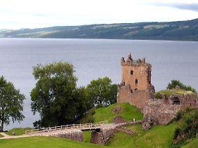Blick auf Loch Ness. Im Vordergrund die Ruinen von Urquhard Castle aus dem 12. Jahrhundert, die auf einer Landzunge bei Drumnadrochit stehen.