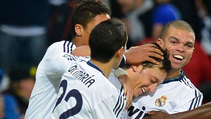 Gute gemacht: Die Kollegen herzen Mesut Özil.