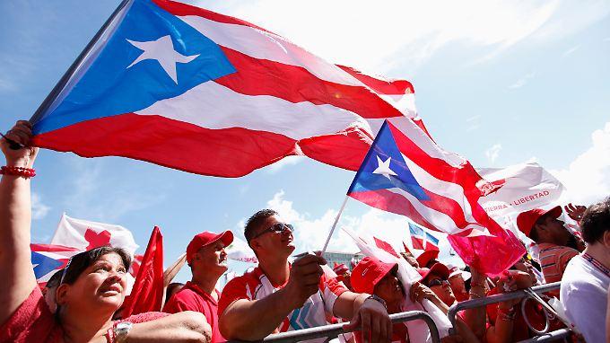Viele Puerto-Ricaner wollen einen eigenen US-Bundesstaat. Diese Einwohner schwenken ihre Fahne allerdings dagegen.