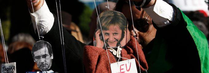 Premierminister Pedro Passos Coelho und Angela Merkel als Marionetten: Die Bundeskanzlerin ist in Portugal nicht überall willkommen.