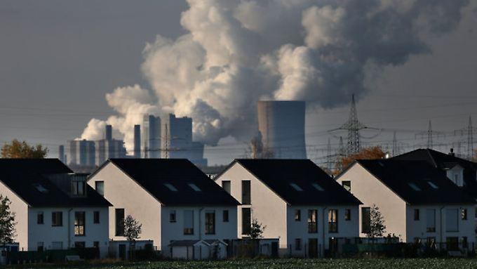 Hinter Wohnhäusern in Köln steigt Dampf aus dem RWE-Braunkohlekraftwerk Neurath auf.
