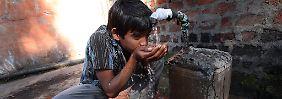 Junge im indischen Bhopal an einem Wasserhahn. Forscher warnen vor globalen Folgen des stetig absinkenden Grundwasserspiegels. Drängend sei die Lage in bestimmten Regionen von Indien, China und den USA.