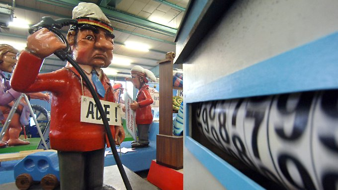 Und es wird immer teurer: Eine Deutsche-Autofahrer-Puppe hält sich die Tankpistole an die Schläfe, während sich die Preisspirale an der Zapfsäule auf einem Karnevalswagen in Mainz weiterdreht. (Archivbild 2006)