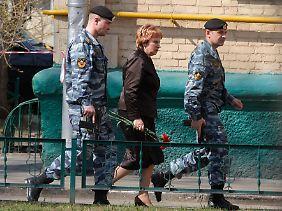Olga Jegorowa, Vorsitzende des Moskauer Stadtgerichts, will in Begleitung ihrer Bodyguards eine Blume am Tatord niederlegen.