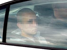 Der jetzt Angeklagte sitzt in Hamburg in einem Polizeiwagen.