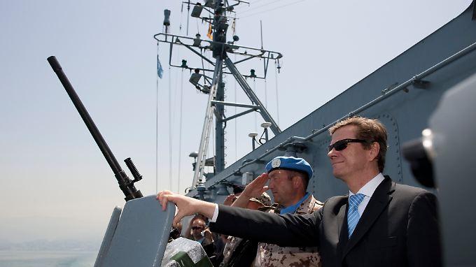 """Außenminister Guido Westerwelle neben Fregattenkapitän Martin Kübel beim Besuch des deutschen Kontingents des UNIFIL-Marine-Verbandes auf dem Minenjagdboot """"Kulmbach""""."""