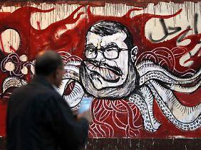 """Eine Abbildung Mursis auf einer Wand des Präsidentenpalastes - mit dem arabischen Aufruf """"Geh"""" versehen."""