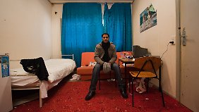 Bescheidener Wohnraum: Ein Asylbewerber aus Indien sitzt in seinem Zimmer in Bad Belzig.