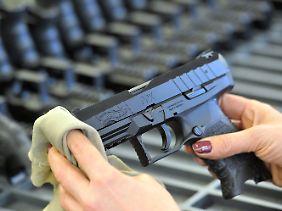 Eine Mitarbeiterin der Firma Walther poliert eine Pistole vom Typ Walther PPX.