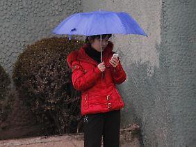 Eine Frau in den Straßen Pjöngjangs hantiert mit ihrem Handy: Sie wird nur innerhalb des Landes telefonieren können. Internetzugang hat sie nicht.