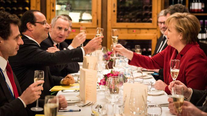Hollande und Merkel stoßen auf die Freundschaft an.