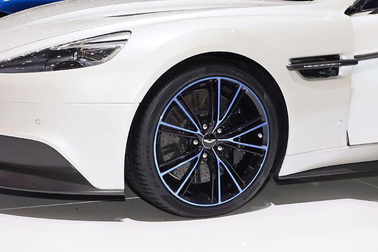 Die zierlichen Felgen des Aston Martin Edelrenners Vanquish wollen so gar nicht zum brachialen Auftritt unter der Haube passen. Schmale, fast zierliche Stege stellen ein V dar und mit dem blau illuminierten Felgenkranz und einzelnen Stegen der Speichen bekommt das Rad etwas von Apple-Hightech.