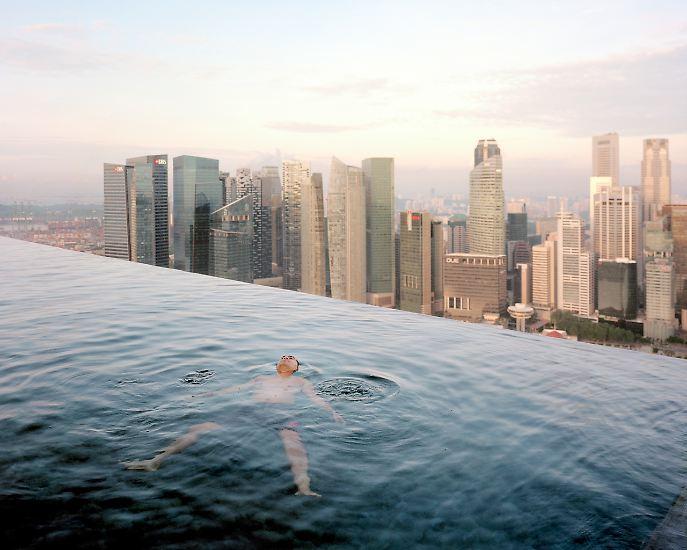 In einer Fotoausstellung begegnen sich zwei Welten: Reich trifft Arm. Hier schwimmt ein Mann im Pool eines Hotels in Singapur.