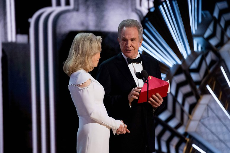 """So hatte sich Warren Beatty die Rückkehr ins Rampenlicht bestimmt nicht vorgestellt: Er steht Ende Februar 2017 mit dem vermeintlichen Sieger-Umschlag auf der Oscar-Bühne. Zögerlich reicht er seiner """"Bonnie und Clyde""""-Kollegin ..."""