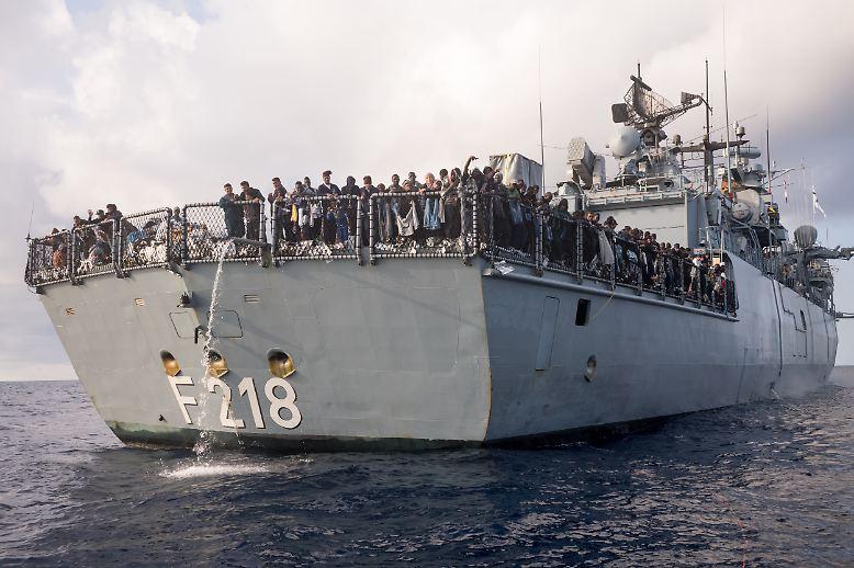 """Nach einer Routine-Untersuchung hält die Fregatte """"Mecklenburg-Vorpommern"""" plötzlich an. Techniker haben im Bug des Schiffes festgestellt, dass Wasser eindringt. Die Flüchtlinge auf dem Flugdeck, die gerade aus Seenot gerettet wurden, bekommen davon zum Glück nichts mit."""