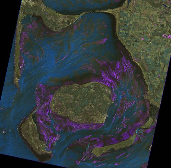Watt vor Sylt: Dieses Bild wurde aus zwei TerraSAR-X-Aufnahmen zusammengesetzt. Eine Aufnahme entstand im April, die andere im Mai 2008. Auf den Wasserflächen weichen sie stark voneinander ab. Das resultierende Bild zeigt Struktur und Beschaffenheit des Watts, der Sedimente und der Lebensräume im Wattenmeer. Deutlich treten Wasserläufe hervor (zu erkennen im blauen Bereich) sowie Muschelbänke (helle Bereiche in Küstennähe).